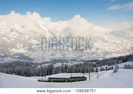View to the Wengernalpbahn railway train passing by the valley in Grindelwald, Switzerland.