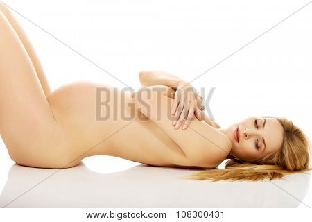 Well groomed pregnant woman lying on the floor