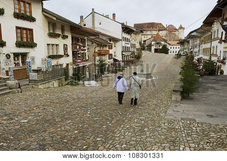 People walk by the street of the medieval town of Gruyeres, Switzerland.