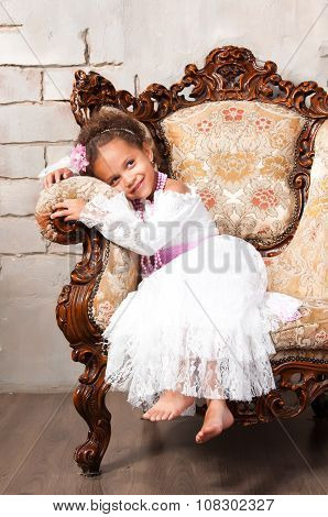 Close-up Portrait Smiling African  Girl In A White Lace Dress On Vintage Chair