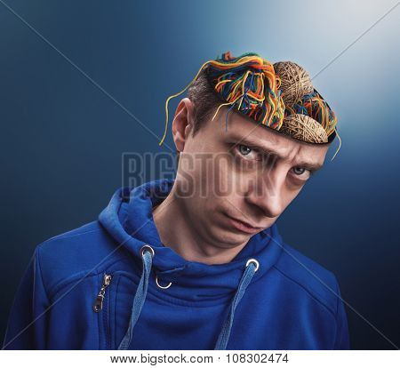 Young man with balls of yarns instead of his brain