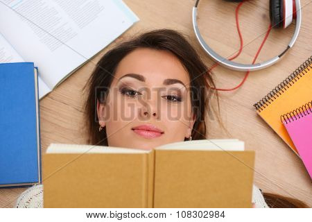 Beautiful Woman Portrait Lying On Floor Reading Book
