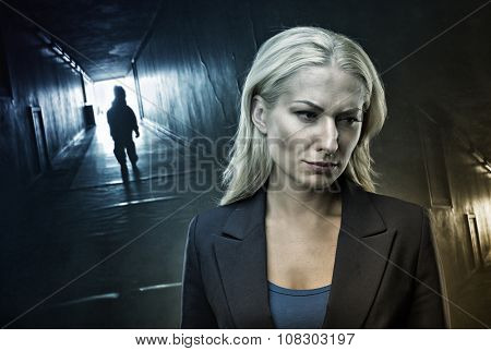 Frustrated blond woman stands in the dark corridor