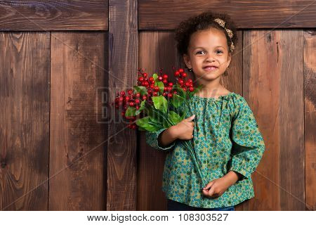 Smiling Little African  Girl In Rural Shirt With Bunch Of Berries On  Background Of Brown Wooden Wal