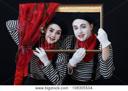 two actors dressed as mimes with Christmas gifts