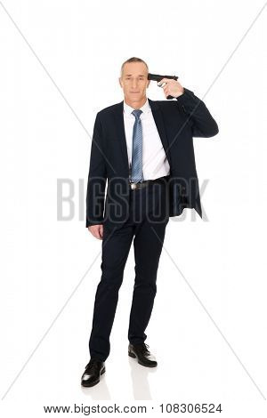 Mature mafia man with handgun near head.