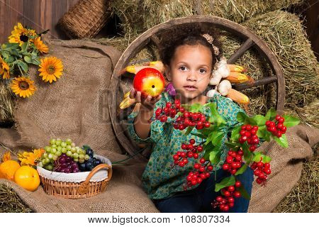Cute  African Girl Sitting On Straw On The Background Of A Wooden Wall