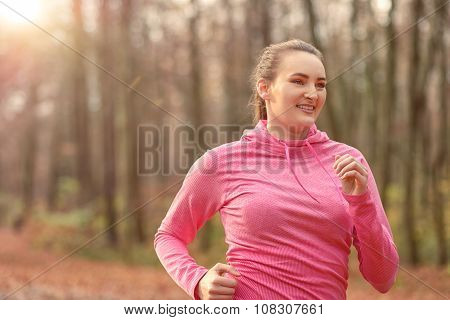 Pretty Fit Young Woman Jogging In Woodland