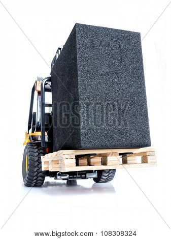 Forklift truck carrying black box placed on wooden pallet shot on white background