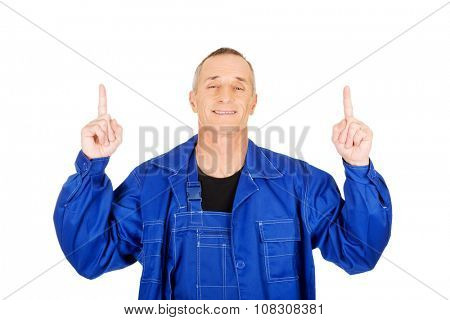 Mature repairman pointing up with both hands.