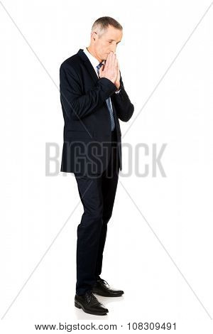 Full length hopeful businessman with clenched hands.