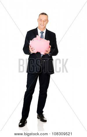 Smiling mature businessman holding big piggybank.