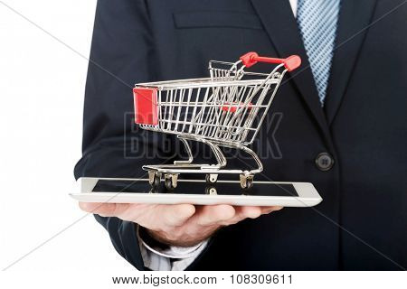 Close up businessman holding shopping cart on tablet.