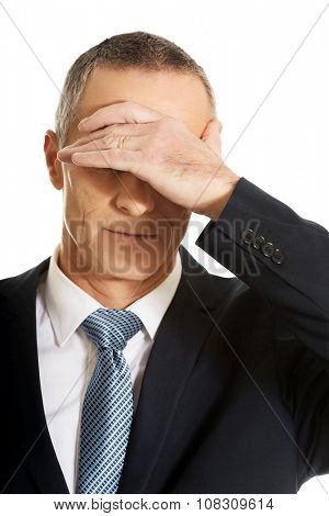 Portrait of stressed businessman covering his face.