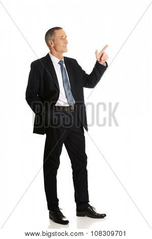 Side view businessman pointing upwards.