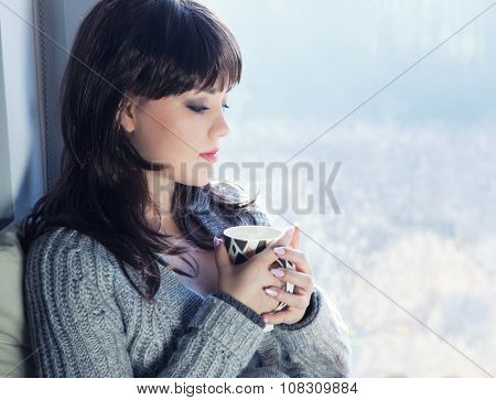 Young beautiful brunette  woman drinking coffee and  wearing knitted cardigan sitting home relaxing by the window. Home chill out concept.