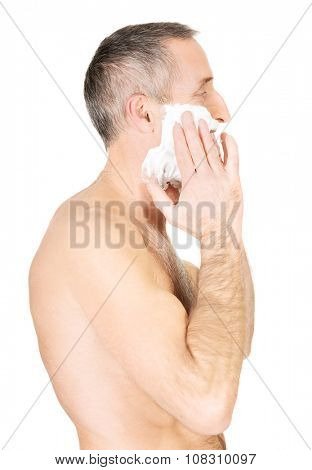 Happy mature man applying shaving foam.