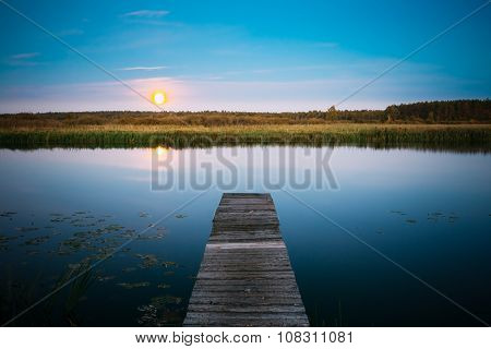 Moonrise over river lake pond in summer evening. Wooden boards p