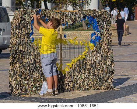 Kiev, Ukraine - September 20, 2015: Boy Weaves Scrim With National Symbols For Military Personnel Ar