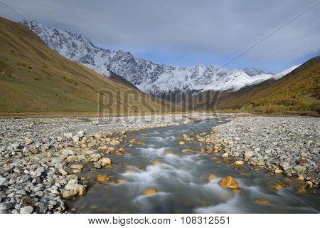 Mountain river. Autumn landscape. Snowy mountain peak. Enguri River and Mount Shkhara. Caucasus, Georgia, Zemo Svaneti