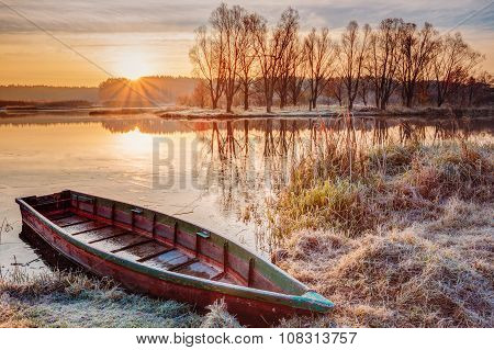 River and rowing fishing boat at beautiful sunrise in autumn morning.
