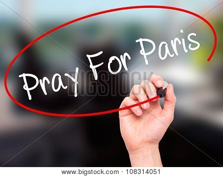 Man Hand writing Pray For Paris with black marker on visual screen.