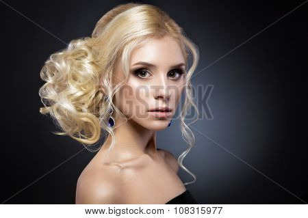 Beautiful blond girl in a black dress with evening haircut  form of waves and bright makeup. Beauty