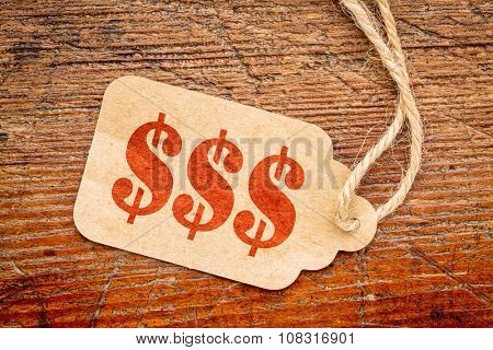 triple dollar sign - red stencil text on a paper price tag against rustic wood