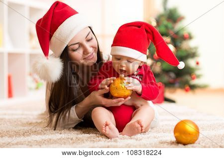 happy mother and adorable baby in suit of Santa