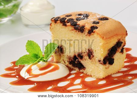 Piece of sponge cake with chocolate chips, cream and caramel sauce on a white plate