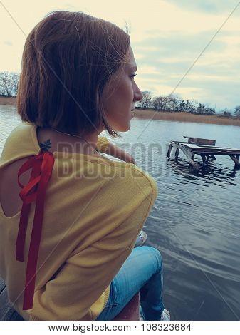 Beautiful girl in the yellow jacket on the bridge of the river coast