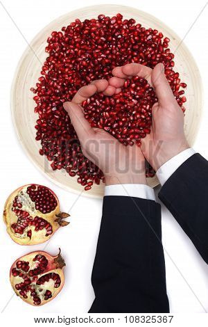 Full Plate Of Peeled Pomegranate Seeds And A Man De-seeding Grenades