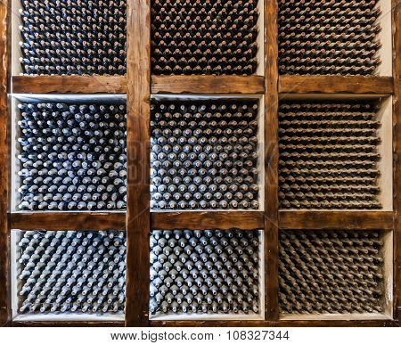 Old bottles of wine maturing in a wine cellar vault