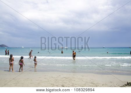 Porto Giunco, Italy-august 23: Unidentified People In Blue Beach With Some People And Grey Cloudy Sk