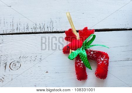Santa Claus Christmas reindeer - red toy with green bow, on white wooden background, empty space for
