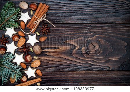 Christmas background with gingerbread cookies fir branches and spices on the old wooden board. Copy