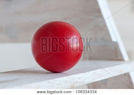 Red plastic ball on white shelf, light background