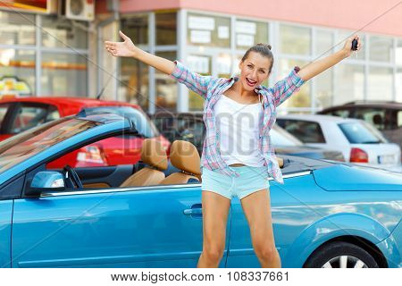 Young Emotional Woman Standing Near A Convertible With The Keys In Her Hand