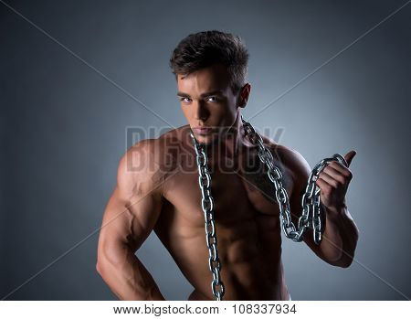 Sexy bodybuilder posing with chain around his neck