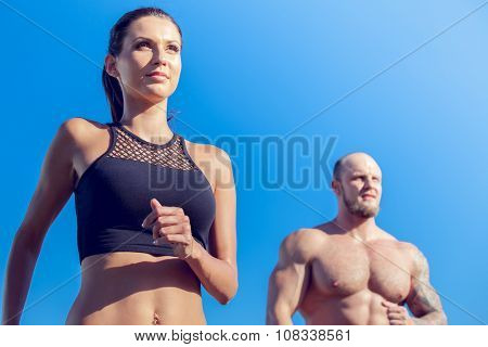 Young strong male and female  fitness models outdoors in beautiful landscape. Man and woman running in park close up