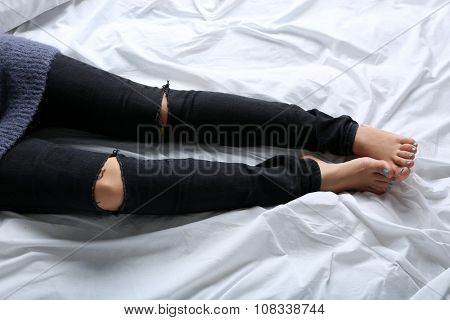 Woman in black jeans on bed top view point