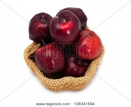 Basket of dark red apples on a white background