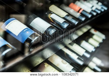 Bottles of wine on the wooden shelf.