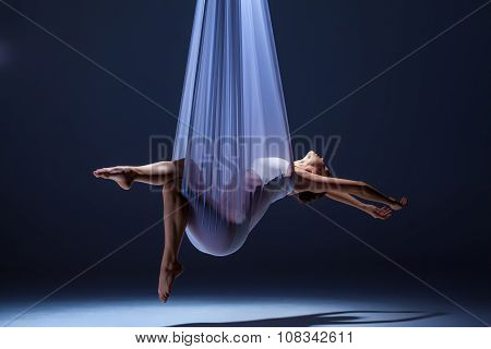 Young beautiful dancer in beige dress posing on gray background