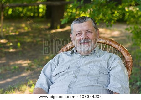 Outdoor portrait of a happy senior man sitting in a chair in summer park