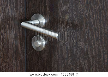 Metallic Door Knob With Lock Over A Wengue Wooden Door