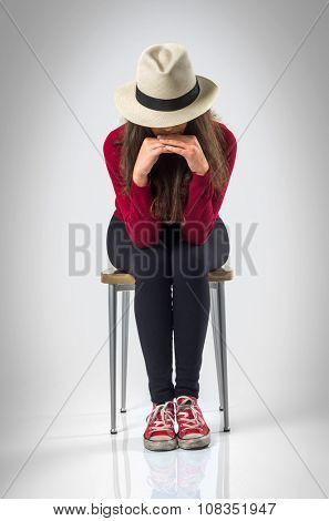 Teenager girl posing in studio wit a chair and a hat over white background