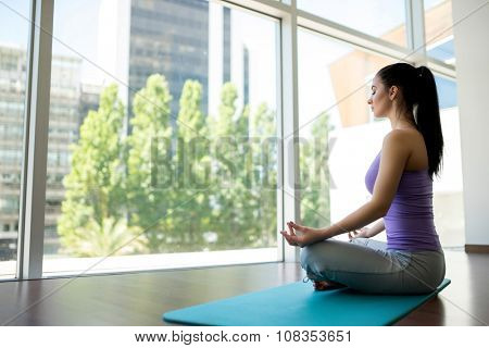 Young girl in lotus pose indoors