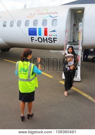 SAINT DENIS, REUNION ISLAND, FRANCE - NOVEMBER 3, 2015: Unidentified immigrant moslem woman with child get off  ATR 72 Air Austral on Roland Garros Airport.