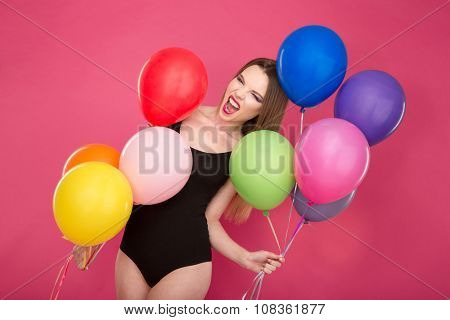 Crazy freaky bizarre screaming young woman in black leotard pozing with colorful balloons on pink background